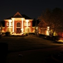 House at night with dramatic exterior lighting and nice landscaping.