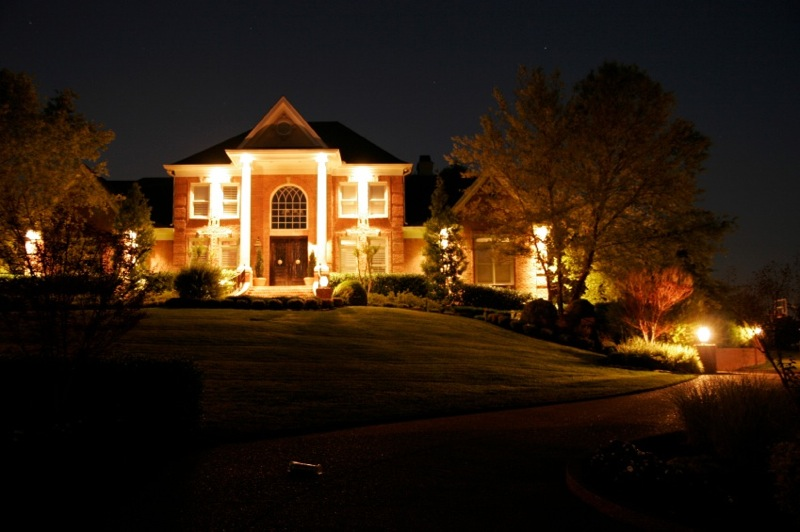 House At Night With Dramatic Exterior Lighting And Nice Landscaping